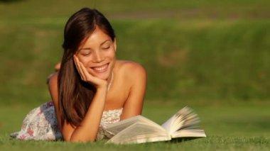 Girl reading book in park smiling happy — Stock Video