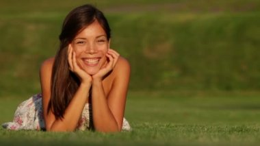 Young beautiful woman smiling lying in grass — Stock Video
