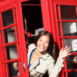 Foto Stock: London red phone booth - woman waving happy