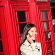 vrouw op smartphone door Londen rode telefooncel — Stockfoto