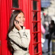Stock Photo: London business woman on smart phone by red booth