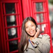 Stock Photo: London woman on smartphone by red phone booth