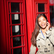 Stock Photo: London woman on smart phone by red phone booth