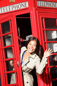 London red phone booth - woman waving happy — Stock Photo