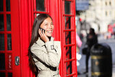 London business woman on smart phone by red booth — Stock Photo