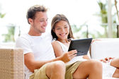 Couple relaxing together in sofa with tablet pc — Stock Photo