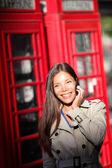 London woman on smartphone by red phone booth — Stock Photo