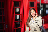 London woman on smart phone by red phone booth — Stock Photo