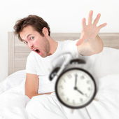 Man waking up late for work early throwing alarm — Stock Photo