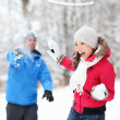 Winter fun - couple in snowball fight — Stock fotografie
