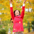 Happy fall woman throwing leaves — Stock Photo