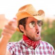 Cowboy man with sunglasses and hat pointing — Stock Photo