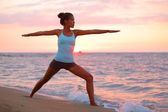 Yoga woman in meditating in warrior pose at beach — Stock Photo