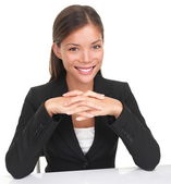Businesswoman sitting at table smiling — Stock Photo