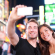 Dating couple happy in love taking selfie photo on Times Square — Stock Photo