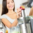 Woman making apple and vegetable juice on juicer — Stock Photo