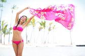 Beautiful woman in bikini on beach waving scarf — Stock fotografie