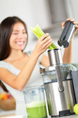 Vegetable juice - woman juicing green vegetables — Stock Photo