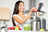 Juicing - woman making apple and vegetable juice — Stock Photo