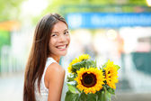 Woman holding sunflower flower smiling happy — Stock Photo