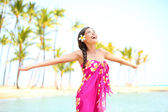 Happy woman praising freedom, palm beach in sarong — Stock Photo