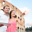 Happy travel couple with tablet by Coliseum, Rome — Stock Photo