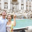Travel couple trowing coin at Trevi Fountain, Rome — Stock Photo