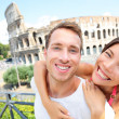 Happy travel couple in piggyback by Coliseum, Rome — Stock Photo #41033899