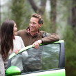 Car people - happy couple driving on road trip — Stock Photo