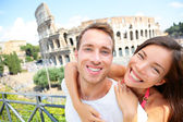 Happy travel couple in piggyback by Coliseum, Rome — Stock Photo