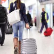 Travel woman walking in an airport with luggage — Stock Photo