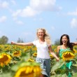Two young women running through sunflowers — Stock Photo #41997503