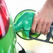 Gas station pump - filling gasoline in green car — Stock Photo
