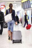 Mujer que camina en un aeropuerto con maletas de viaje — Foto de Stock