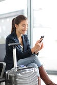 Airport woman on smart phone at gate - air travel — Stock Photo