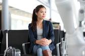 Airport woman waiting in terminal - air travel — Stock Photo