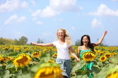 Two young women running through sunflowers — Stock Photo