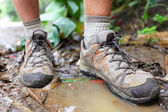 Hiking shoes on hiker in water puddle — Stockfoto