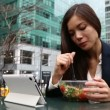 Business woman using tablet pc eating salad — Stock Video