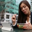 Businesswoman using tablet computer eating salad — Stock Video
