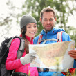 Hiking couple looking at map hiking in forest — Stock Photo