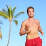 Beach man running smiling happy in swimwear — Stock Photo