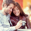 Happy young couple looking at pictures on camera — Stock Photo #44256271