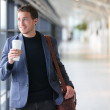 Businessman drinking coffee walking in airport — Stock Photo #44256663