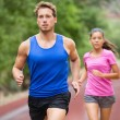 Running couple jogging on road — Stock Photo