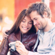 Couple looking at pictures on camera — Stock Photo #44258755