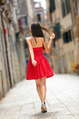 Woman in red dress walking in street in Venice — Stok fotoğraf