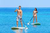 Pessoas de praia Paddleboard no levantar placa de remo — Fotografia Stock