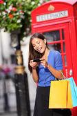 Londra kadın akıllı telefon alışveriş üzerinde — Stok fotoğraf