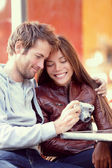 Happy young couple looking at pictures on camera — Stock Photo